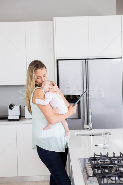 Mother using digital tablet while carrying her baby in kitchen Stock photo © wavebreak_media