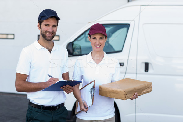 Portrait of delivery man and woman standing with clipboard and parcel Stock photo © wavebreak_media