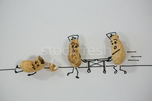 Peanut figurine providing medical assistance tom injured peanut figurine Stock photo © wavebreak_media