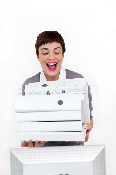 Radiant businesswoman putting a pile of folders on a desk  Stock photo © wavebreak_media