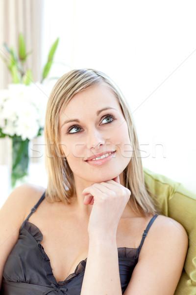 Radiant woman sitting on a sofa  Stock photo © wavebreak_media