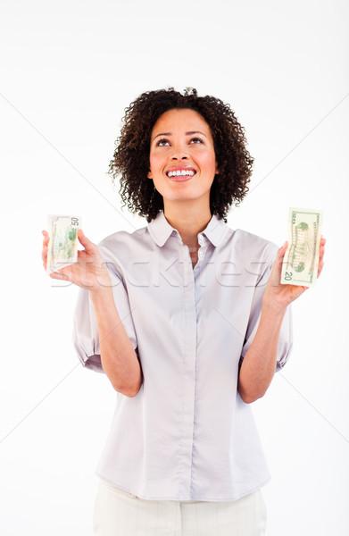 Smiling businesswoman holding dollars and looking upwards Stock photo © wavebreak_media