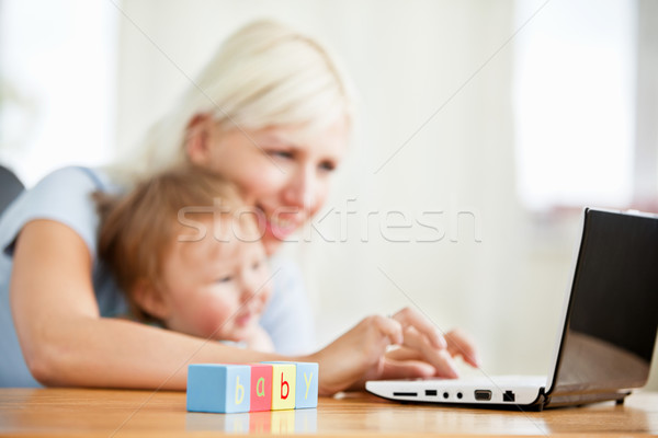 Smiling woman surfing on the internet with her girl in the living-room at home Stock photo © wavebreak_media