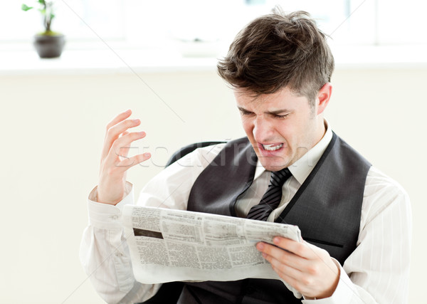 Portrait of a annoyed businessman reading a newspaper in the office against white background Stock photo © wavebreak_media
