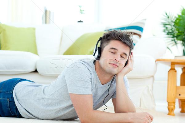 Charmant jonge man luisteren muziek vloer woonkamer Stockfoto © wavebreak_media