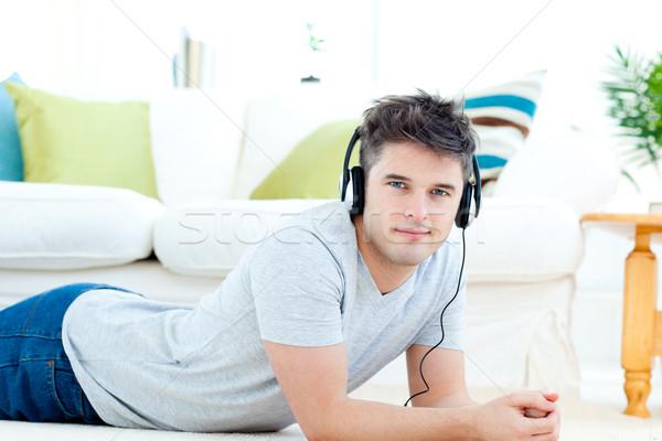 Knappe man hoofdtelefoon vloer woonkamer muziek glimlach Stockfoto © wavebreak_media