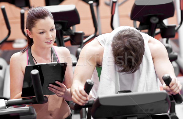 Exhausted man doing exercises while his coach is looking at his results in a sport centre Stock photo © wavebreak_media