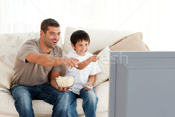 Stock photo: Happy father and son watching television while eating pop corn at home