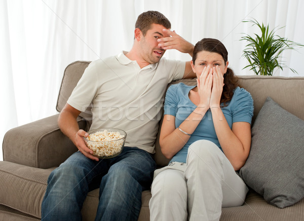 Scared couple eating pop corn while watching a horror movie at home Stock photo © wavebreak_media
