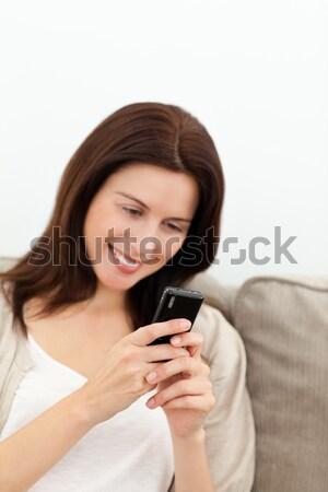 Heureux femme un message canapé Photo stock © wavebreak_media