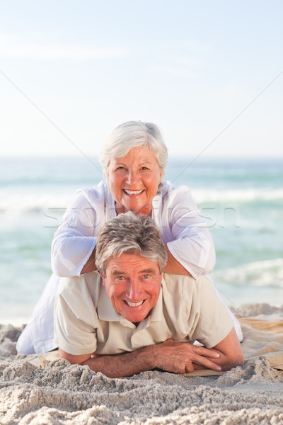 Stock photo: Elderly couple lying down on the beach