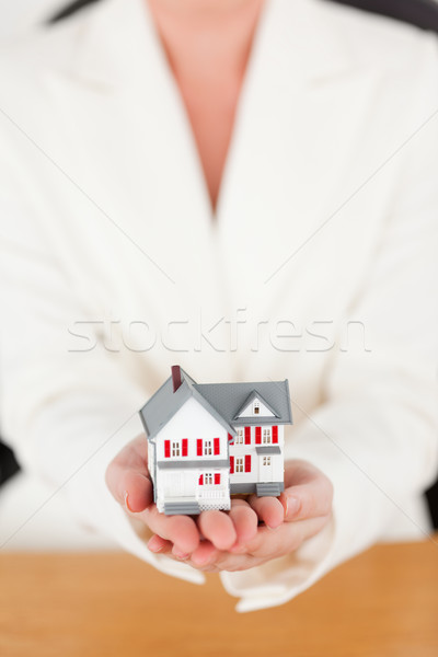 Young pretty red-haired female in suit holding a miniature house while sitting in an office Stock photo © wavebreak_media