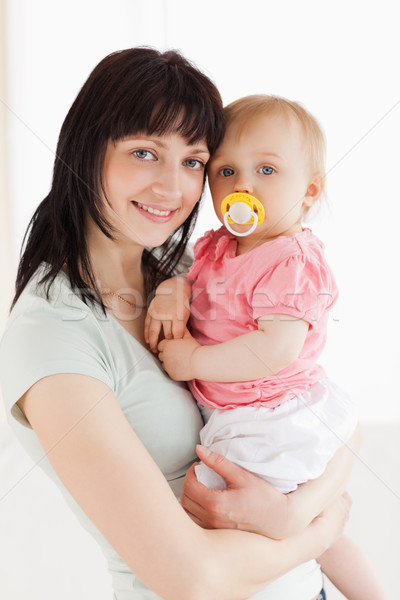 Good looking woman holding her baby in her arms while standing in the living room Stock photo © wavebreak_media