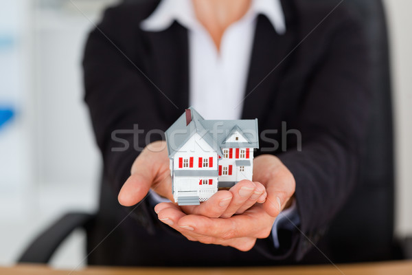 Feminine hands holding a miniature house in an office Stock photo © wavebreak_media