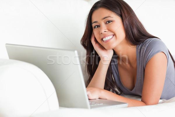 happy woman lying on sofa with notebook smiling into camera in livingroom Stock photo © wavebreak_media