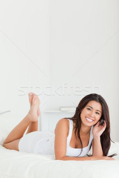 beautiful woman lying on bed with crossed legs looking into camera in bedroom Stock photo © wavebreak_media