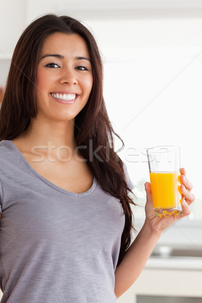 Beautiful woman holding a glass of orange juice while standing in the kitchen Stock photo © wavebreak_media