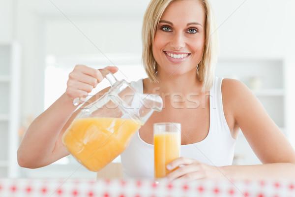 Femme souriante séance table remplissage jus d'orange Photo stock © wavebreak_media