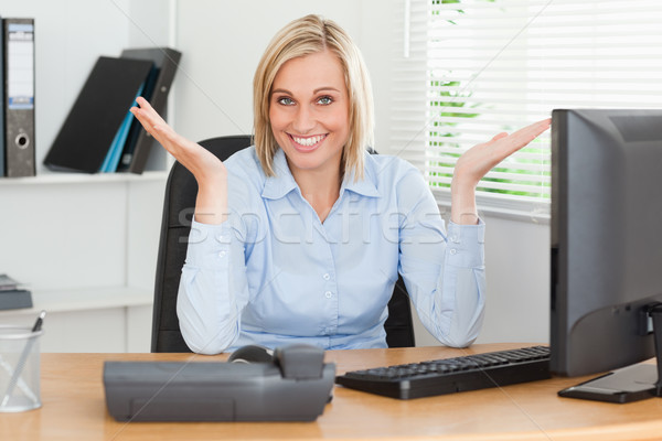 Smiling blonde woman sitting behind desk not having a clue what to do next in an office Stock photo © wavebreak_media