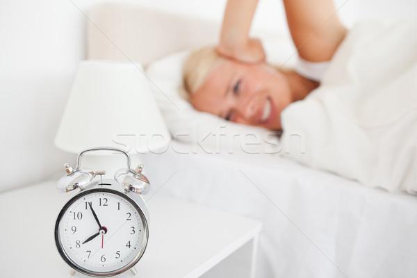 Angry woman awaken by her alarnclock in her bedroom Stock photo © wavebreak_media