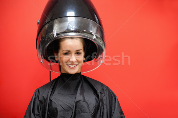 Stock photo: Woman under a hairdressing machine against a red background