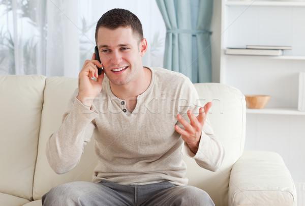 Homme parler téléphone séance canapé salon Photo stock © wavebreak_media
