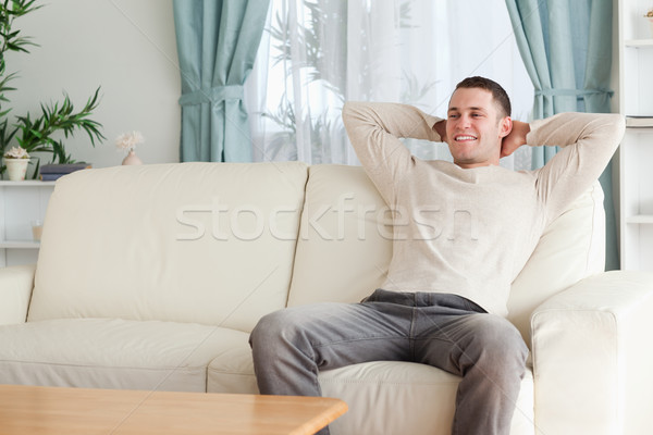 Happy man relaxing on a couch in his living room Stock photo © wavebreak_media