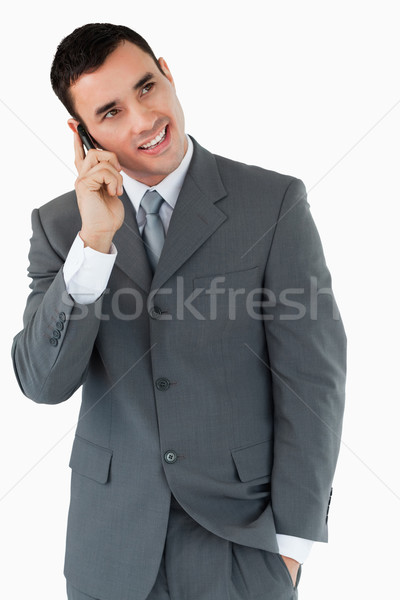 Smiling businessman looking diagonally upwards while on the phone against a white background Stock photo © wavebreak_media