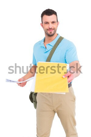 Smiling young delivery man with parcel and delivery note against a white background Stock photo © wavebreak_media