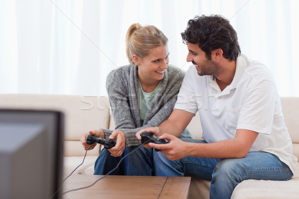 Stock photo: Happy couple playing video games in their living room
