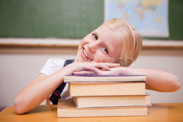 Smiling girl leaning on books in a classroom Stock photo © wavebreak_media