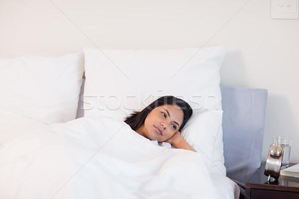 Fiatal nő bámul ébresztőóra otthon szépség ágy Stock fotó © wavebreak_media