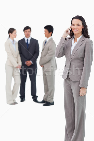 Smiling saleswoman on her cellphone with team behind her against a white background Stock photo © wavebreak_media
