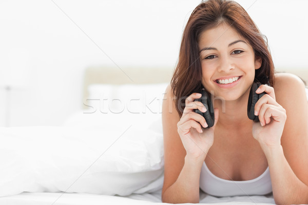 A woman at the end of the bed smiling and looking forward with earphones around her neck, listening  Stock photo © wavebreak_media