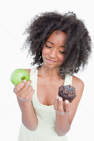 Young woman hardly hesitating between a chocolate muffin and a green apple Stock photo © wavebreak_media