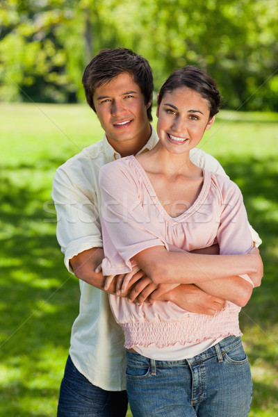 Man and woman smiling as he has his arms around her abdomen in a park Stock photo © wavebreak_media