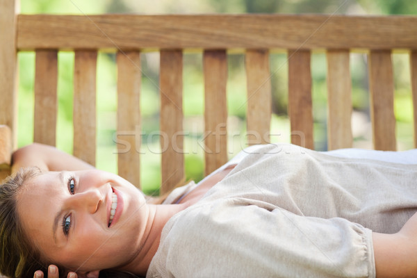 Smiling young woman lying on a park bench Stock photo © wavebreak_media