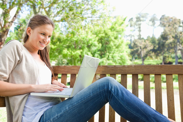Oldalnézet mosolyog fiatal nő pad laptop szépség Stock fotó © wavebreak_media