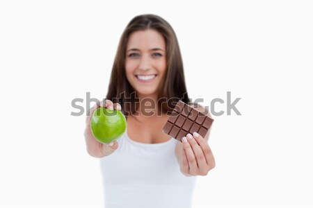 A green apple and chocolate being held by a woman against a white background Stock photo © wavebreak_media