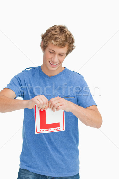 Young man ripping a learner driver sign against white background Stock photo © wavebreak_media