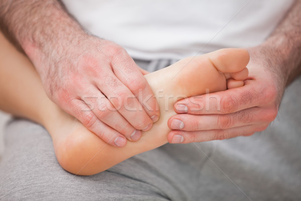 Podiatrist massaging the foot of a woman while holding it on his thigh indoors Stock photo © wavebreak_media