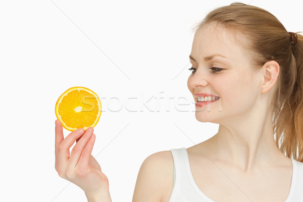 Woman presenting an orange slice while looking at it against white bakground Stock photo © wavebreak_media