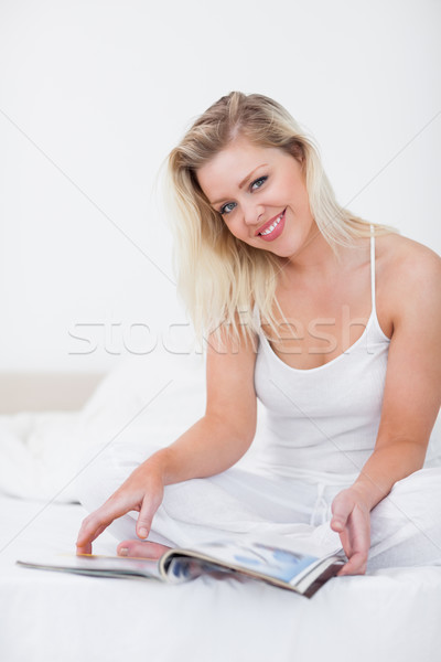 Blonde smiling with a magazine on a bed Stock photo © wavebreak_media