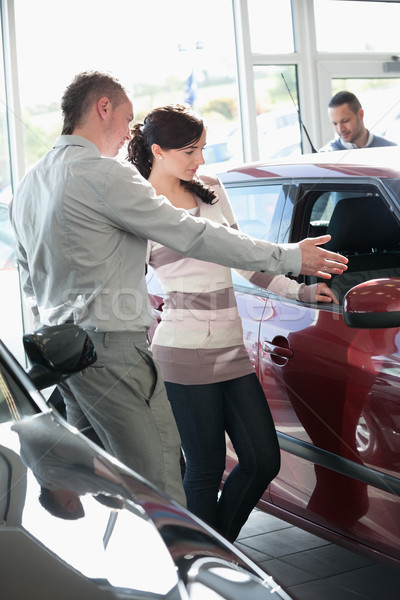 Woman looking at a car interior being pointed by a salesman Stock photo © wavebreak_media