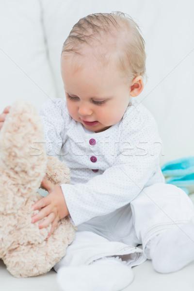 Baby touching a teddy bear in living room Stock photo © wavebreak_media