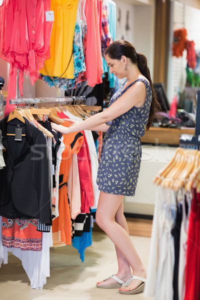 Woman standing at a clothes rack in the shop looking through clothes Stock photo © wavebreak_media