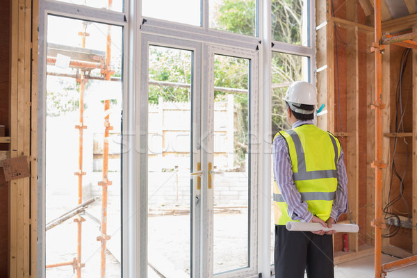 Architect holding a plan while looking outside and standing in the house Stock photo © wavebreak_media