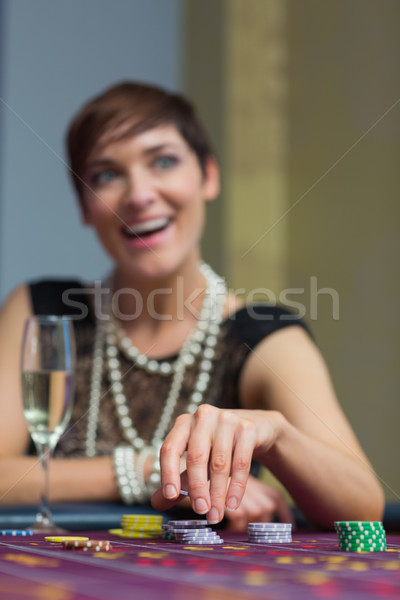 Woman sitting holding chips at roulette table in casino Stock photo © wavebreak_media