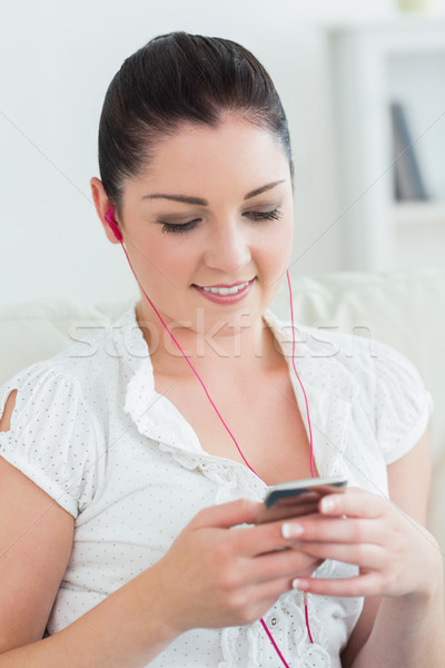 Smiling woman sitting on the couch in a living room and listening to music Stock photo © wavebreak_media