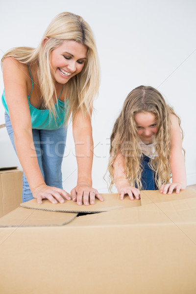 Mother and daughter laughing and closing moving boxes Stock photo © wavebreak_media